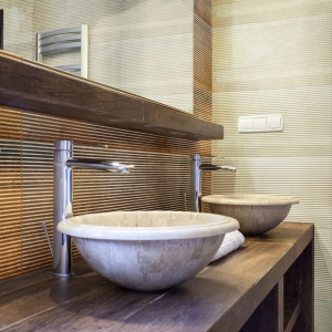 Rdzawe struktury i kamienne szarości w aranżacji łazienki