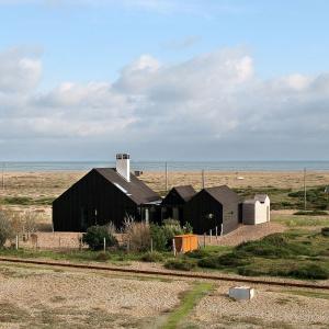 Czarno-biała chatka rybacka na kamienistej plaży