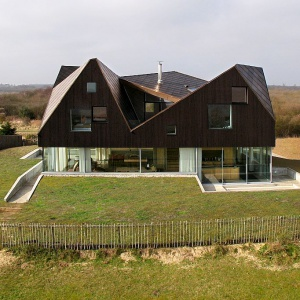 Dom na wydmach. Szklany parter dźwiga masywny dach